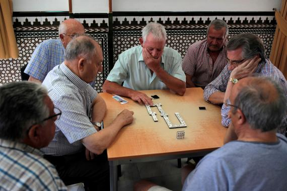 Grupo de pensionistas jugando al dominó