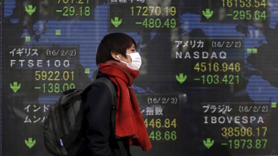 Un hombre con mascarilla pasa ante las pantallas de mercados de la Bolsa de Tokio