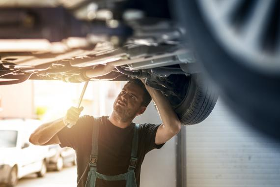 Un hombre repara un coche.