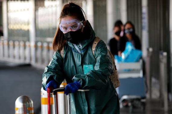 Una mujer en el aeropuerto, con mascarilla y gafas de protección