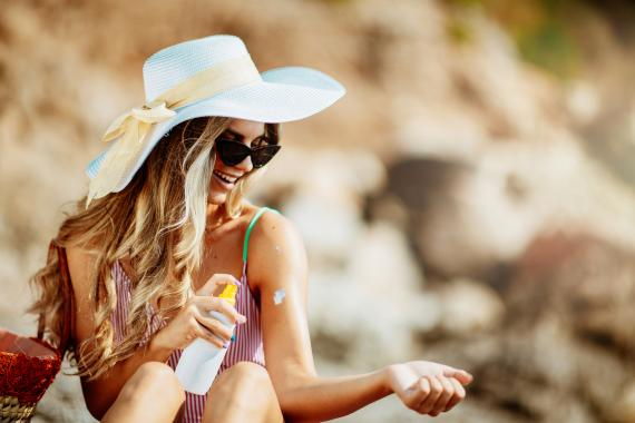 Una mujer se aplica protector solar.