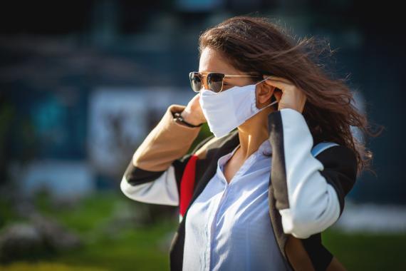 Una mujer colocándose la mascarilla.