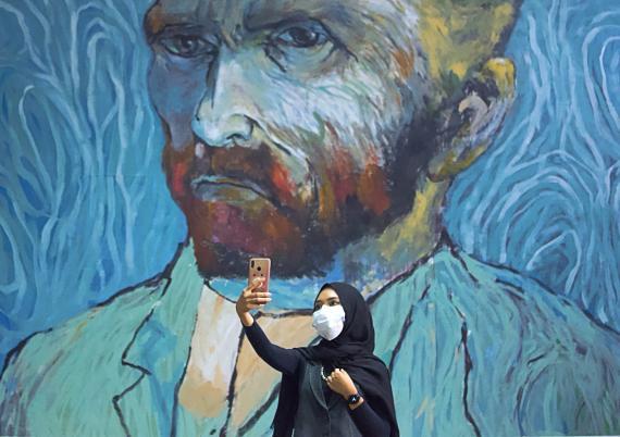 Una mujer se hace un selfie con un mural en medio de la pandemia de coronavirus