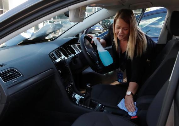 Una mujer limpia el interior de su vehículo.