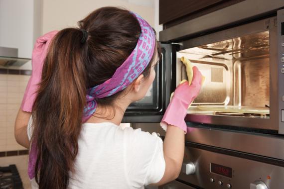 Mujer limpiando el microondas