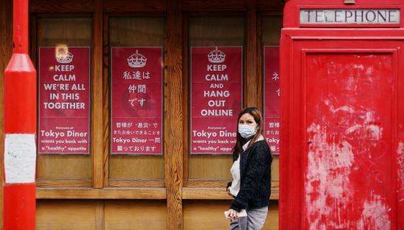 Una mujer con mascarilla pasa ante un negocio cerrado por coronavirus en Londres (Reino Unido)