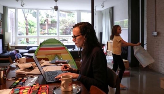 Una mujer teletrabaja mientras su hija juega en su apartamento en Nueva York (EEUU)