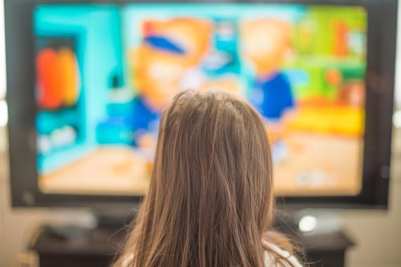 Una niña frente a una pantalla de televisión