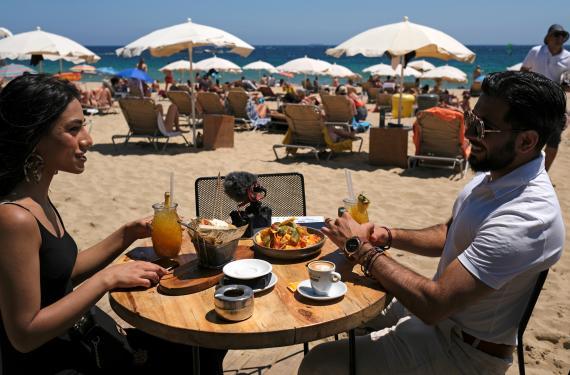 Una pareja en una terraza de la playa de la Barceloneta durante la pandemia del coronavirus
