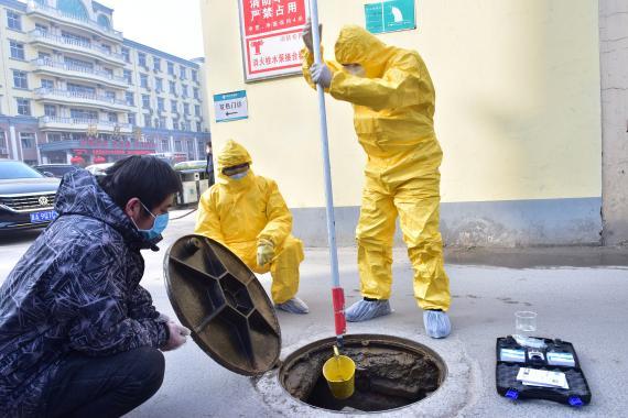 Trabajadores recogen muestras de aguas residuales tras un brote de coronavirus en China.