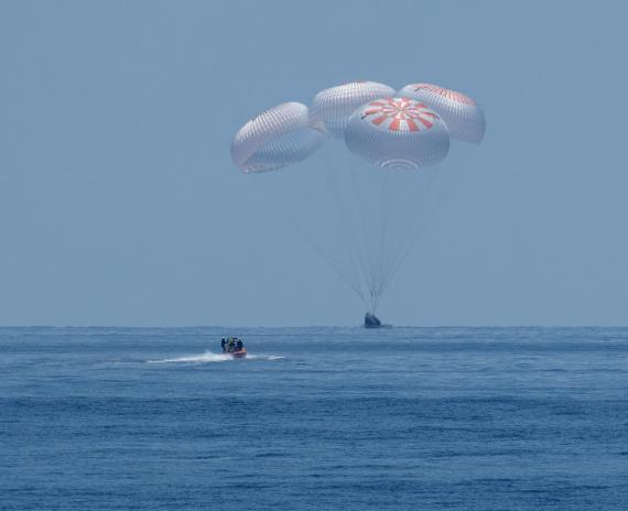La cápsula en la que viajaban los astronautas aterrizando en la Tierra.