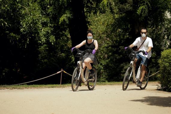 Dos personas pasean con bicicletas de BiciMad, el sistema público del Ayuntamiento de Madrid, en plena pandemia del coronavirus.