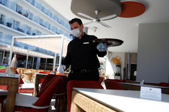 Un camarero en un bar con mascarilla