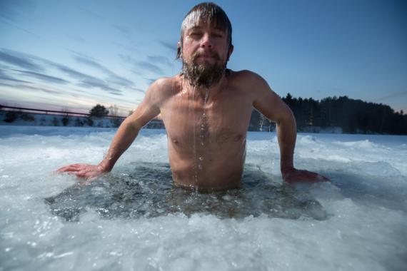 Hombre bañándose en un lago helado.