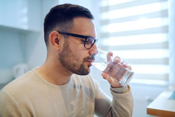 Hombre bebiendo agua en un vaso.