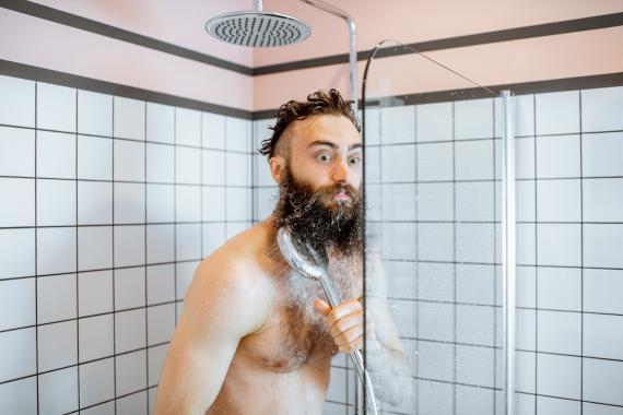 Hombre dándose una ducha fría.