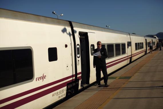 Un trabajador de Renfe espera a que los viajeros se suban al tren en Ronda, Málaga.
