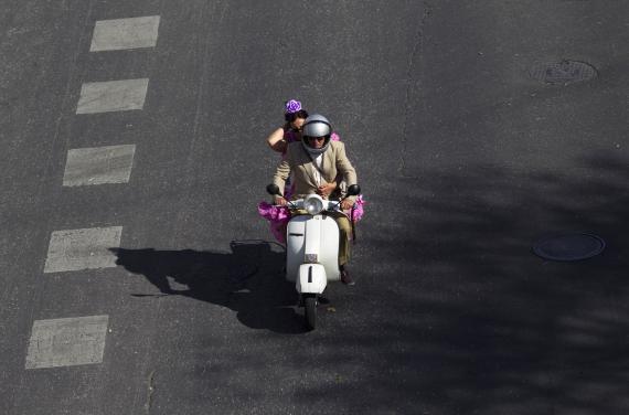 Un hombre y una mujer conducen una moto en Sevilla.