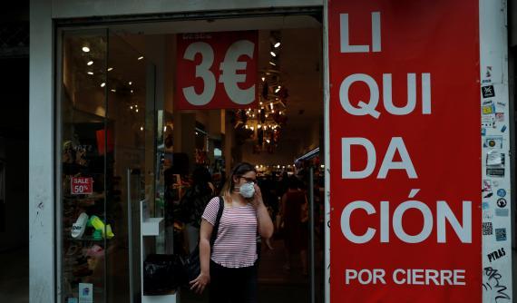 Una mujer se ajusta su mascarilla a la salida de una tienda en liquidación por cierre en Madrid
