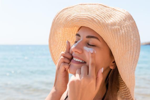 Una mujer se aplica crema después de tomar el sol.
