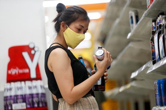 mujer comprando cerveza en el supermercado