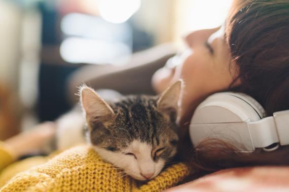 Una mujer escucha música con su gato.