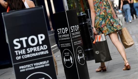 Una mujer pasa ante 2 anuncios sobre las precauciones contra el coronavirus en Londres