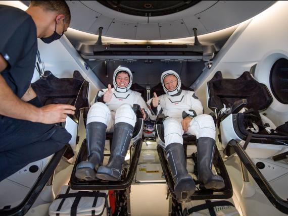 Los astronautas de la NASA Bob Behnken y Doug Hurley dentro de la nave espacial Crew Dragon de SpaceX en la nave de recuperación, poco después de haber salpicado en el Golfo de México cerca de Pensacola, Florida, el domingo