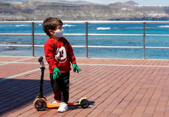 Un niño con mascarilla juega con un patinete en medio de la pandemia del coronavirus