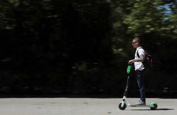 Un hombre utiliza un patinete eléctrico compartido de Lime, Madrid.