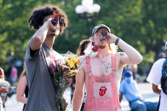 People remove their masks to drink beer in Washington Square Park on August 9, 2020, in New York City. Alexi Rosenfeld/Getty Images