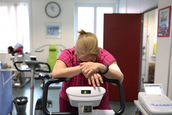 Sandra Cabreras, 57, rides an exercise bike to strengthen muscle tone while suffering from post-COVID fatigue. Marco Di Lauro/Getty Images