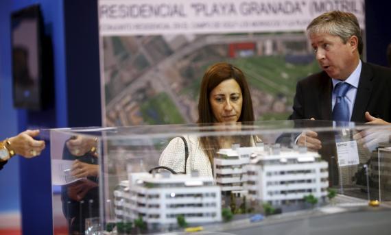 Un agente inmobiliario presenta una promoción de viviendas a varios clientes en una feria en Madrid