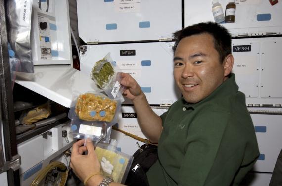 El austronauta Akihiko Hoshide prepara la comida durante una misión de la NASA en el espacio.