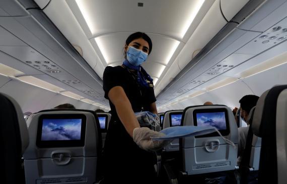 Azafata repartiendo mascarillas en un avión durante la pandemia del coronavirus
