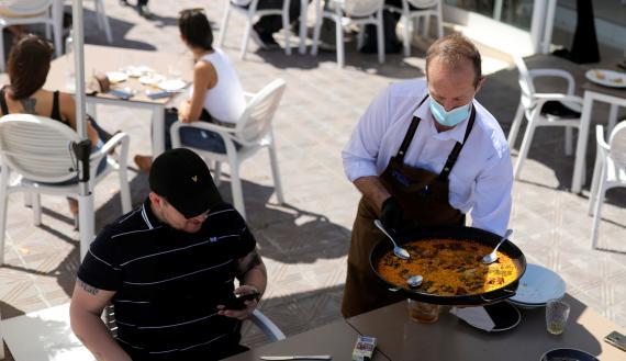 Un camarero sirve paella en una terraza de Valencia