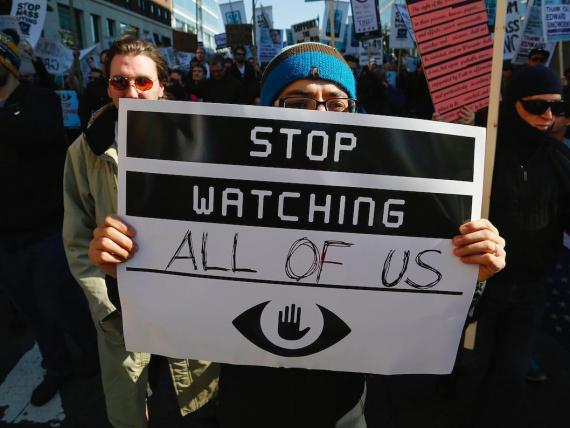 """A demonstrator holds up a sign at the """"Stop Watching Us: A Rally Against Mass Surveillance"""" march near the U.S. Capitol in Washington, October 26, 2013.  REUTERS/Jonathan Ernst"""