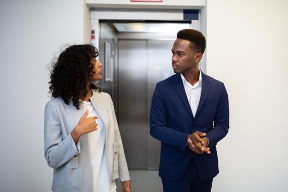 Dos personas hablando a la salida del ascensor.