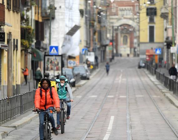 Dos riders de Glovo y Deliveroo realizan un reparto en Milán.