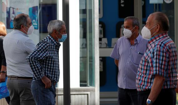 Un grupo de jubilados con mascarilla conversan en una calle de Ronda (Málaga)