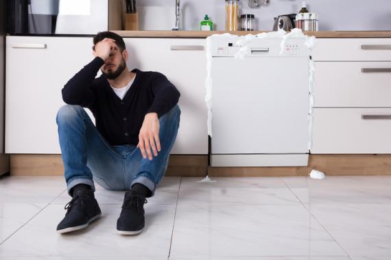 Hombre lamentándose por un lavavajillas estropeado.