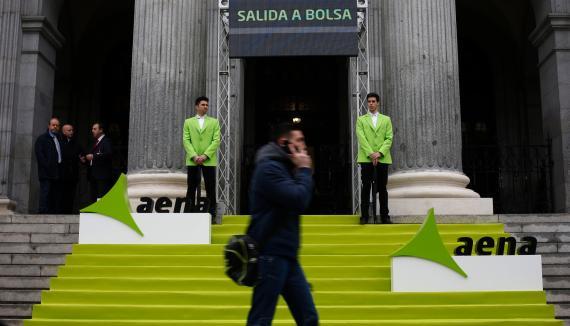 Un hombre pasa ante la Bolsa de Madrid durante el debut de Aena en el Ibex 35