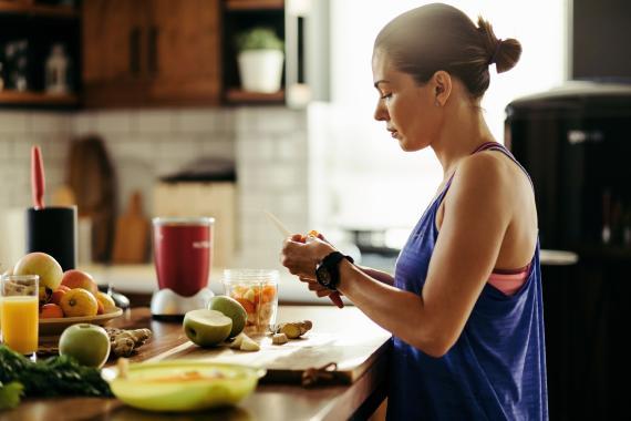 Una mujer cocina comida saludable.