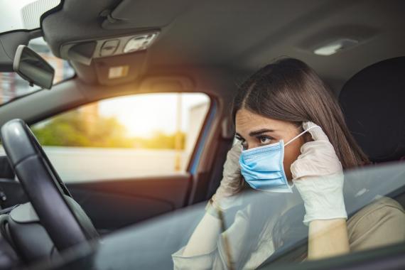 Una mujer se coloca la mascarilla dentro del coche.