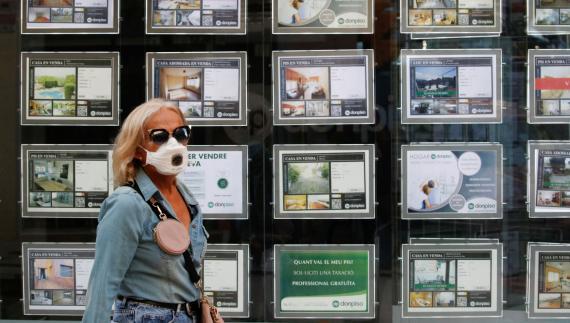 Una mujer con mascarilla pasa ante la fachada de una inmobiliaria con anuncios de pisos en venta y alquiler