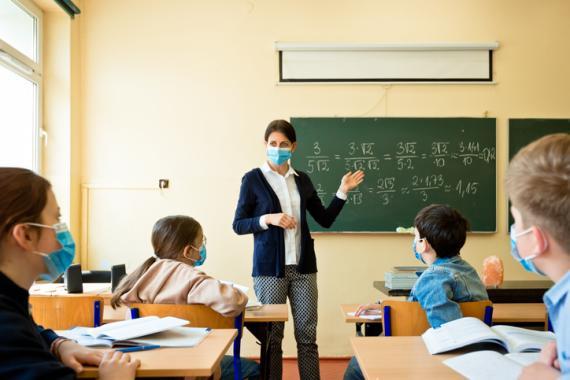 NIños y profesora con mascarilla en el colegio.