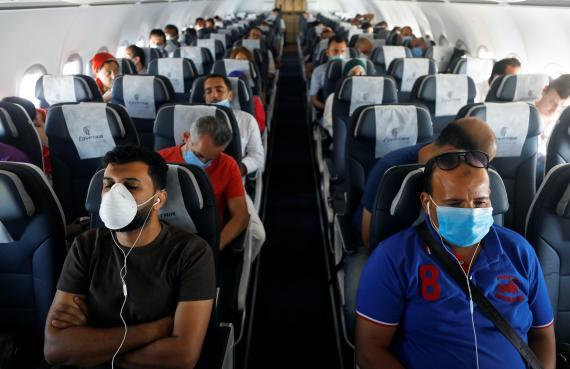 Pasajeros llevan mascarillas en un avión en el Aeropuerto Internacional de Sharm el-Sheij, en Egipto.