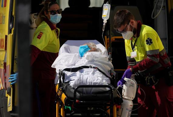Sanitarios meten a un paciente en camilla dentro de una ambulancia.