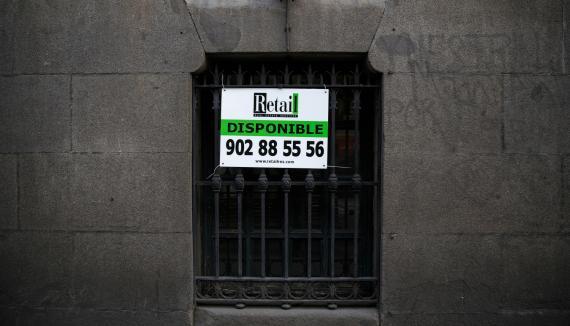 Un anuncio de una inmobiliaria en la ventana de un bajo en Madrid