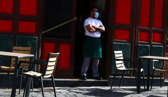 Un camarero con mascarilla ante una terraza vacía en Madrid